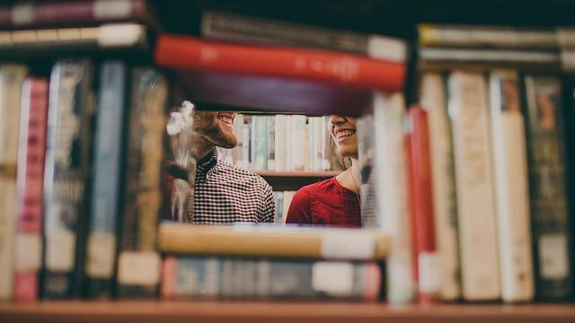 Photo d'une fille et d'un graçon souriant dans une bibliothèque