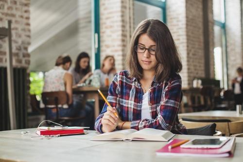 Photo d'une étudiante qui étudie en salle d'étude
