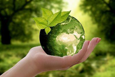 Photo d'une main tenant une goutte d'eau contenant le monde - Le tout sur fond de nature
