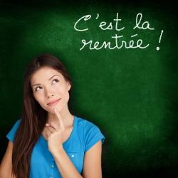 """Photo d'une étudiante qui pose devant un tableau vert sur lequel il est écrit """"C'est la rentrée"""""""