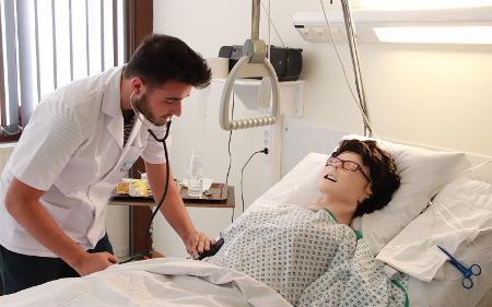 Photo d'un étudiant en soins infirmiers avec le patient automate du Sim'HERS