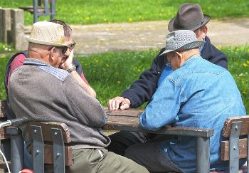 Photo de seniors qui jouent à une table en plein air