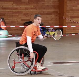 Photo d'un étudiant en chaise roulante qui joue une variante du tennis