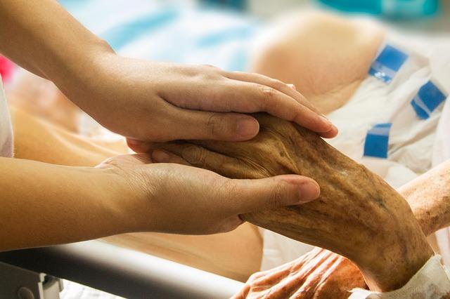 Photo de la main d'un patient âgé dans les mains du d'une infirmière
