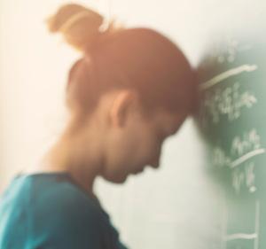 Photo d'une étudiante qui se tape la tête au tableau